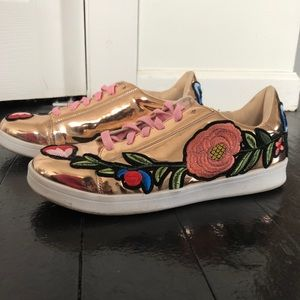 Gold sneakers with floral embellishments